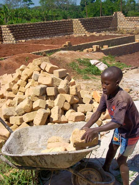 A child helps lay the foundation for the school in Buwasa which was built with funds from Global Playground.
